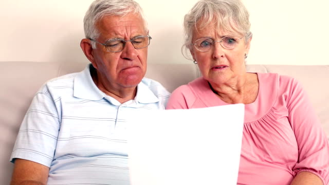 Worried senior couple reading a document video