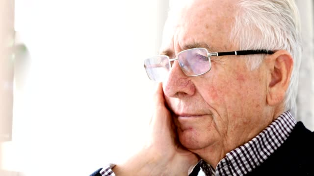 Worried Senior Man Sitting In Chair At Home video