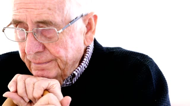 Worried Senior Man With Walking Stick Sitting In Chair At Home video