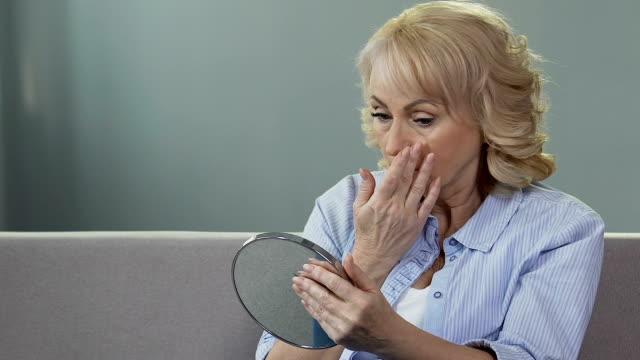 orolig senior kvinna som tittar på sin spegelbild i spegel, plastikkirurgi, åldrande - mänsklig ålder bildbanksvideor och videomaterial från bakom kulisserna