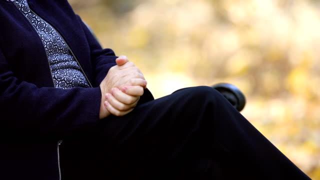 vídeos de stock e filmes b-roll de worried senior woman rubbing her hands outdoors closeup - rachado