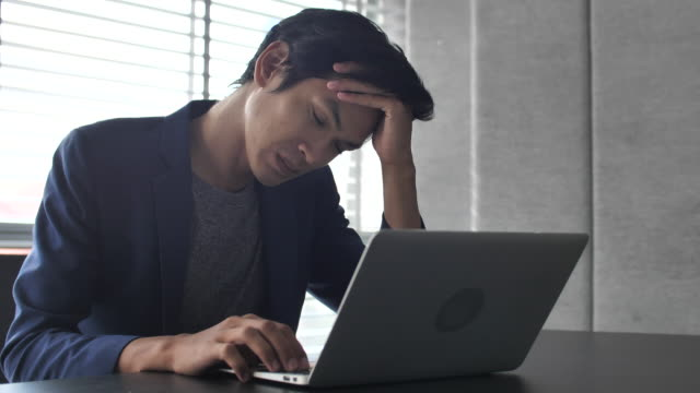 Worried serious businessman working on laptop in office Worried serious businessman working on laptop in office east asia stock videos & royalty-free footage