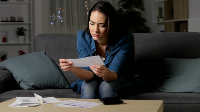 vidéos et rushes de femme inquiet vérifiant des reçus de banque dans la nuit - bec
