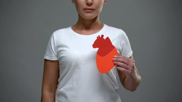 vídeos de stock e filmes b-roll de worried woman holding paper heart sign, prevention of stroke and heart attack - coração fraco