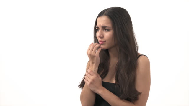 Worried woman rubs hand in hand. Rubbing palms gesture. Model biting her nails. Isolated, on white background