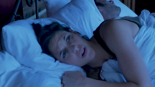 Worried woman unable to sleep in bed at night Worried attractive woman in her late 20s or early 30s unable to sleep in bed at night trying to get comfortable next to a man insomnia stock videos & royalty-free footage