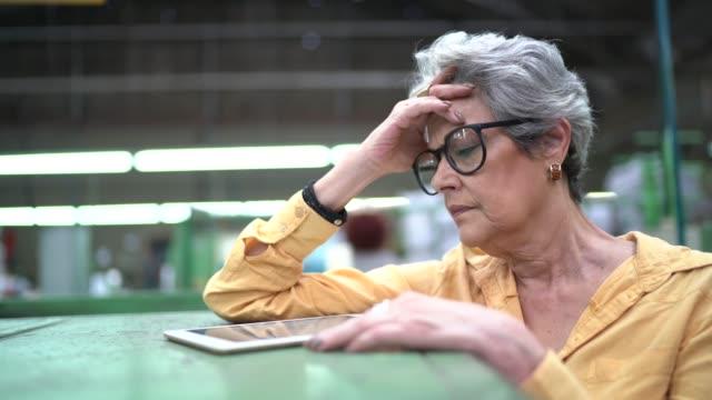 stockvideo's en b-roll-footage met bezorgde vrouw die in de fabriek werkt - gewichten