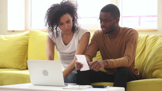 Worried young african american couple calculate bills discuss financial problem Worried young african american couple calculate bills pay online on laptop discuss financial problem high taxes expenses, black family stressed about paperwork talk about unpaid bank debt bankruptcy bankruptcy stock videos & royalty-free footage