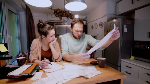 Worried young family looking at their bills in the kitchen at home. Man and woman calculating domestic accounts video