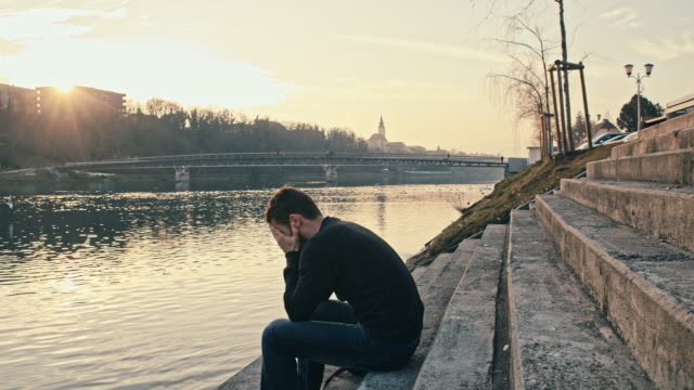stockvideo's en b-roll-footage met ws worried young man by the river - liefdesverdriet