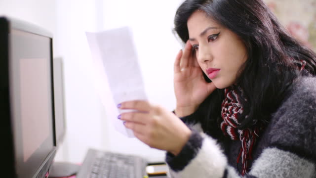 Worried young woman paying bills on computer.