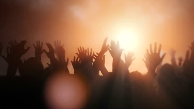 Worship crowd Silhouettes of hands raised in worship with sunlight. prayer stock videos & royalty-free footage