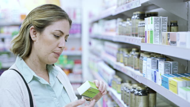 Worth a try 4k video footage of a young woman browsing the shelves of a pharmacy antibiotic stock videos & royalty-free footage