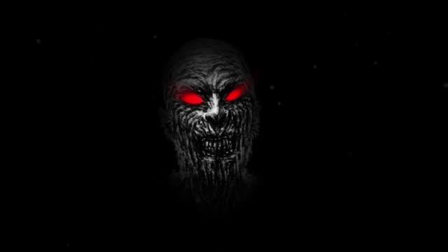 wounded zombie face with red eyes on black background. - potwór filmów i materiałów b-roll