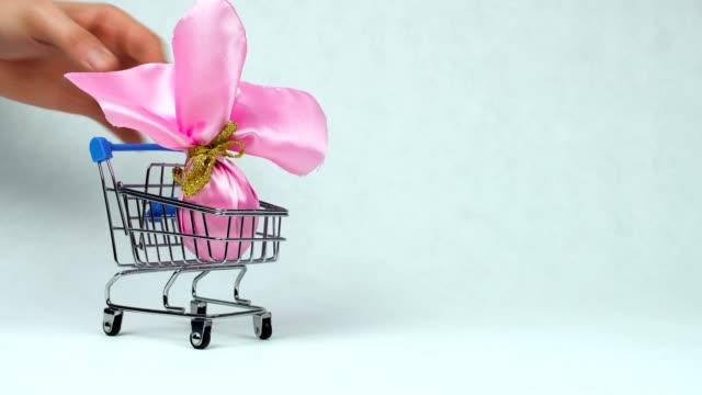 贈り物として包まれたイースターエッグは、日曜日にパスチャやキリスト教のごちそう復活の間におもちゃのショッピングカートに入れ - イースター点の映像素材/bロール