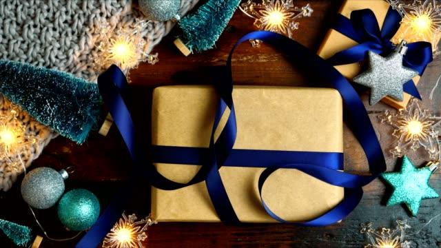 confezione regali di natale su tavolo in legno scuro, stop motion nightime. - christmas table video stock e b–roll