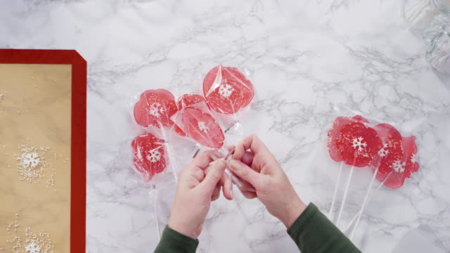 Wrapping large homemade lollipops into clear gift bags.