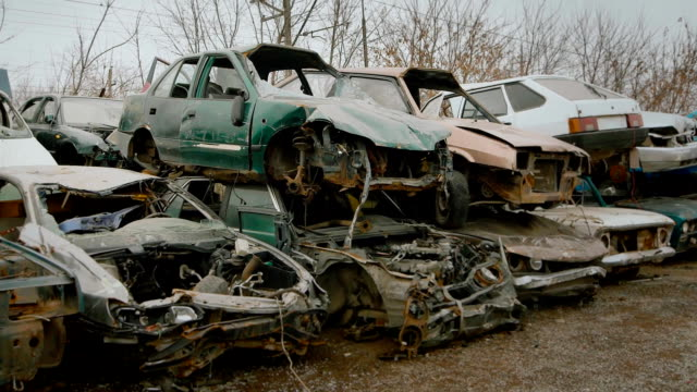 Wrecked vehicles are placed on top of one another on junkyard video