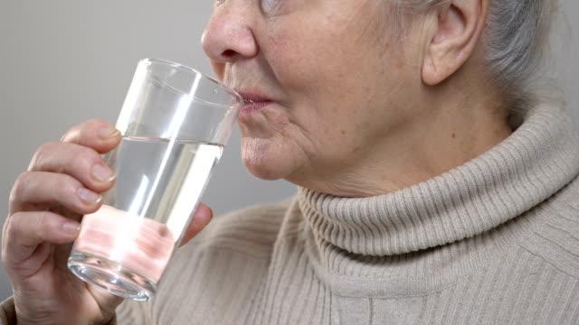 Agua potable de anciana arrugada, sensación de sed, tomar medicina, closeup - vídeo