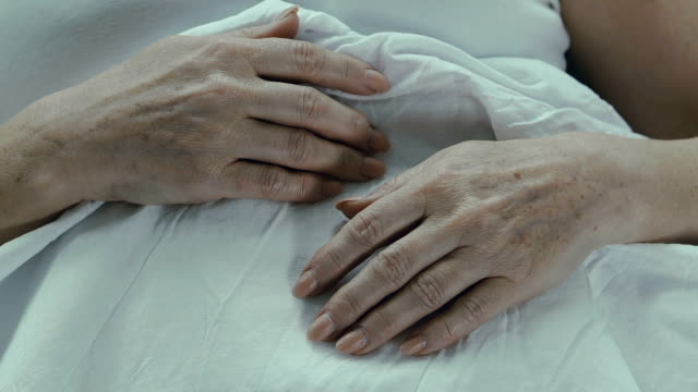 Wrinkled hands of senior woman lying on stomach, incurable disease, unhealthy video