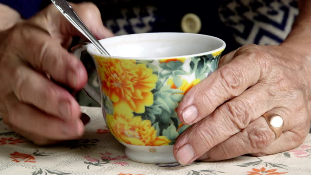 wrinkled hands of senior woman with cup of drink close-up - tea cup stock videos & royalty-free footage