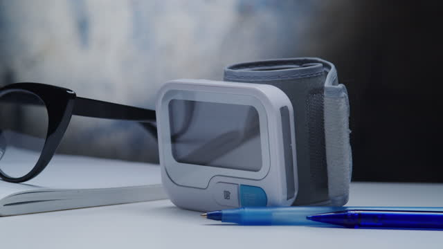 Wrist type  blood pressure monitor, note pad, eyeglasses and pen on the desk video