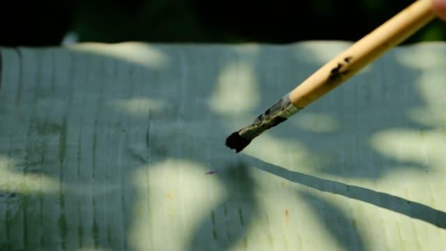 バナナの葉に禅の円を書く、自然サイクルの概念 - 習字点の映像素材/bロール