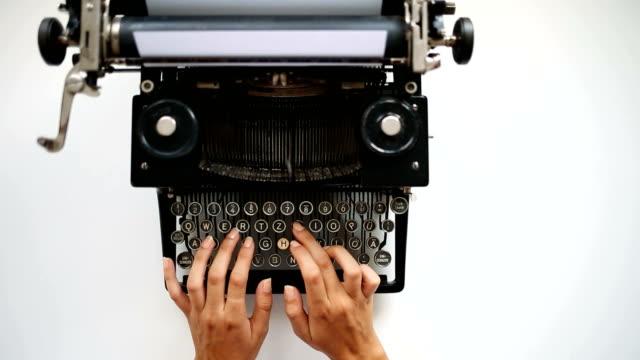 Writer prints on retro typewriter High angle view of secretary prints on vintage typing machine. typewriter stock videos & royalty-free footage