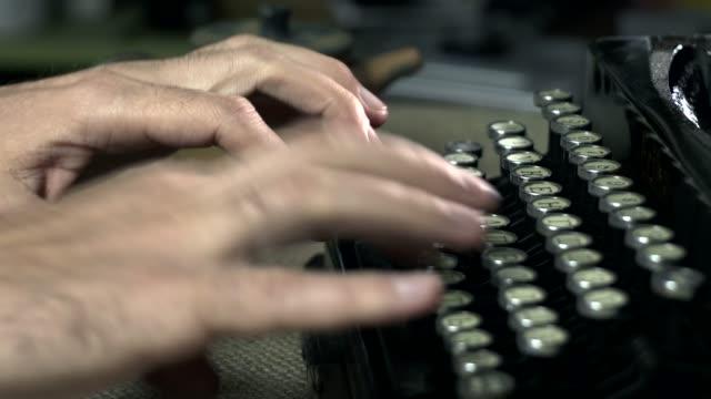 writer types on typewriter keyboard