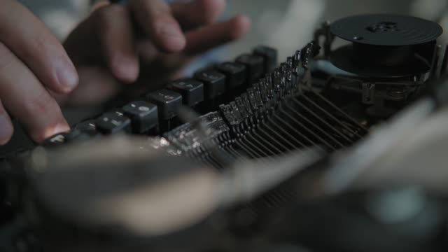 Writer typing on a typewriter, taken from side. Vintage scene Writer typing with retro writing machine. Sun lights on the hand. Typing on a typewriter, taken from side. Vintage scene of 60-70's, historical reenactment concept. typewriter stock videos & royalty-free footage