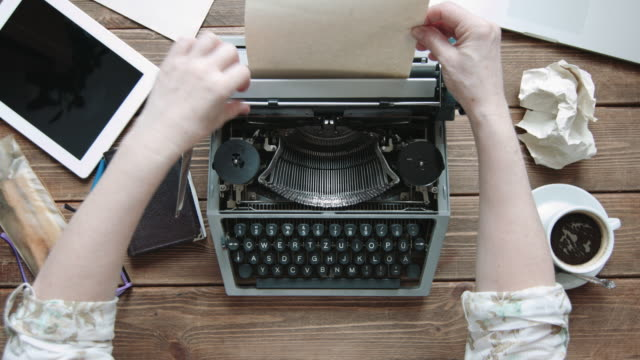 Writer with retro writing machine. Writer refill paper in old typewriter. View from above. typewriter stock videos & royalty-free footage