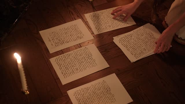 writer woman in night shirt is writing poem in a dark room with a candle light