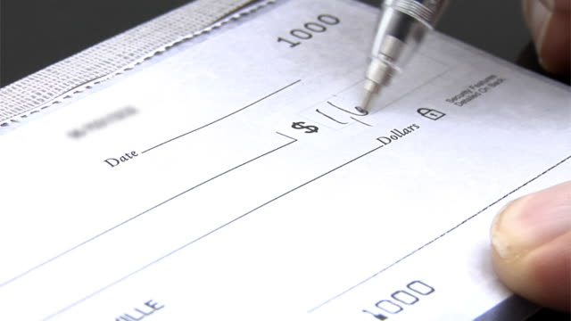 Writing a check, closeup video