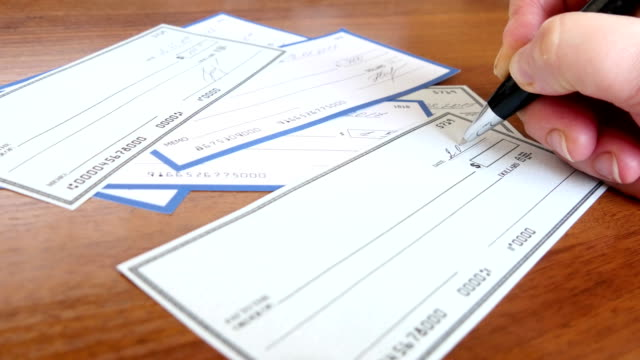 Writing a check for payment with a ballpoint pen