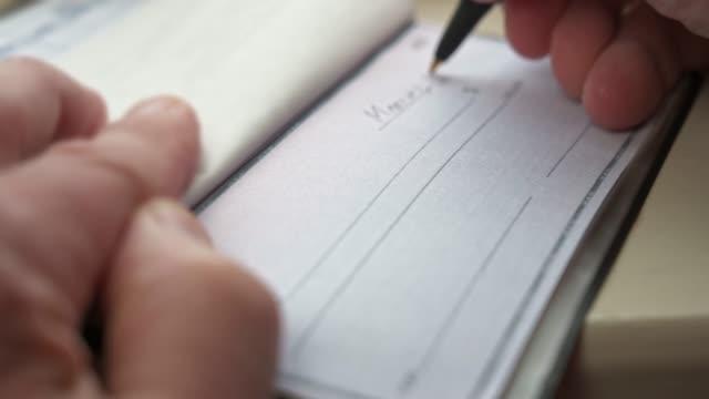 vídeos de stock, filmes e b-roll de escrevendo um cheque - escrever