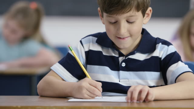 Writing a Test An elementary aged boy writes with pencil during school with his classmates. He smiles as though the work is easy. mathematics stock videos & royalty-free footage