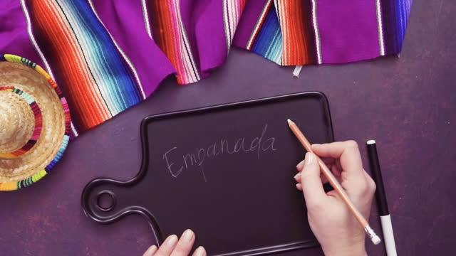 Writing Emapanadas sign on black chalk board.