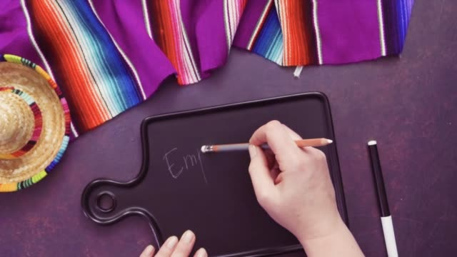 Writing Empanadas sign on black chalk board.