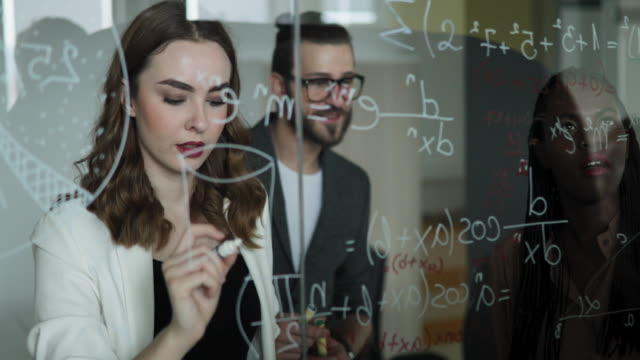 Writing Mathematical Formulas On Glass Board Scientists Writing Mathematical Formulas On Glass Board Using Liquid Chalk mathematics stock videos & royalty-free footage