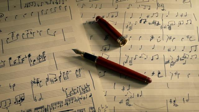 vídeos de stock e filmes b-roll de writing music concept - ink pen on sheet music - compositor