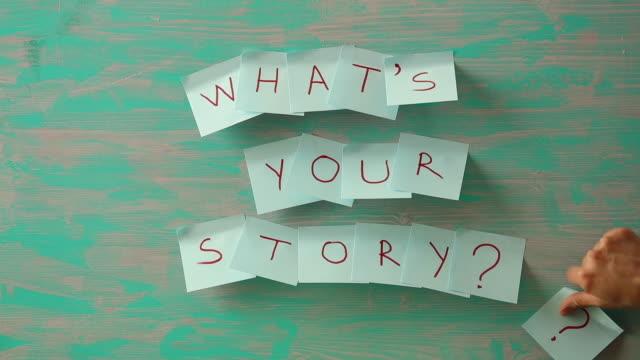 schreibnote, die was ihre geschichte in frage zeigt. - storytelling videos stock-videos und b-roll-filmmaterial