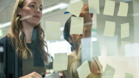 vidéos et rushes de écrire des notes pour la nouvelle stratégie plan - brainstorming