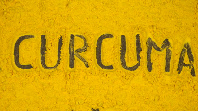 TOP VIEW: Writing of curcuma word on a yellow curcuma background - Stop motion animation video