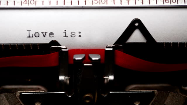 Writing short phrase 'Love is' with an old Typewriter