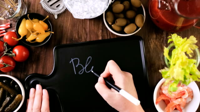 Writing sign for Bloody Mary bar on black cutting board video