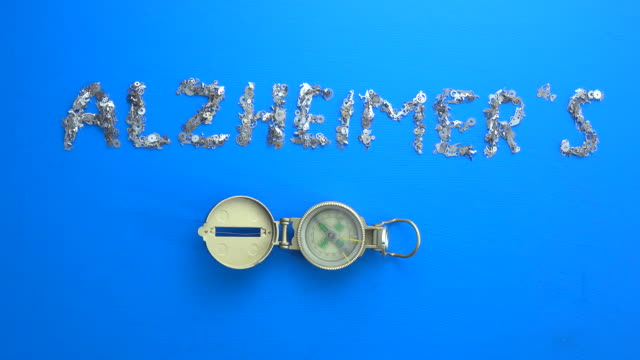 Writing Word ALZHEIMER'S With Metal Clockworks On blue background video