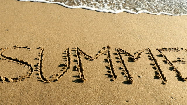 SUMMER written in sand Hd slow motion close-up video of Single word SUMMER written in golden sand on Mediterranean beach. Text message handwritten in the water's edge where sea waves splashing. Sunny weather, peace on the earth, idyllic vacations. Space for copy, camera stabilization video, no people. beach party stock videos & royalty-free footage