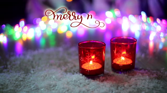 Written Merry merry Christmas vintage text on decor background with candles and multicolors lights. Calligraphy and lettering flourish elements. holiday video