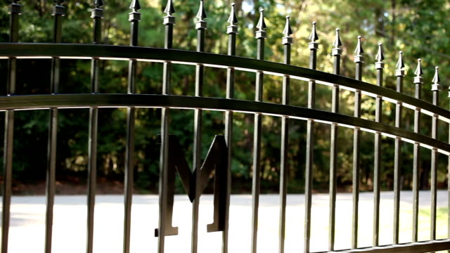Wrought iron gate opening to the left. Home driveway. An automatic, wrought iron gate opening to the left in front of a home's driveway.  A neighborhood road and trees are in background.  No people. gate stock videos & royalty-free footage