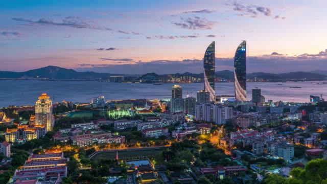 t/l ws ha zo xiamen city skyline och amoy twin towers från skymning till natt/xiamen, fujian-provinsen, kina - xiamen bildbanksvideor och videomaterial från bakom kulisserna